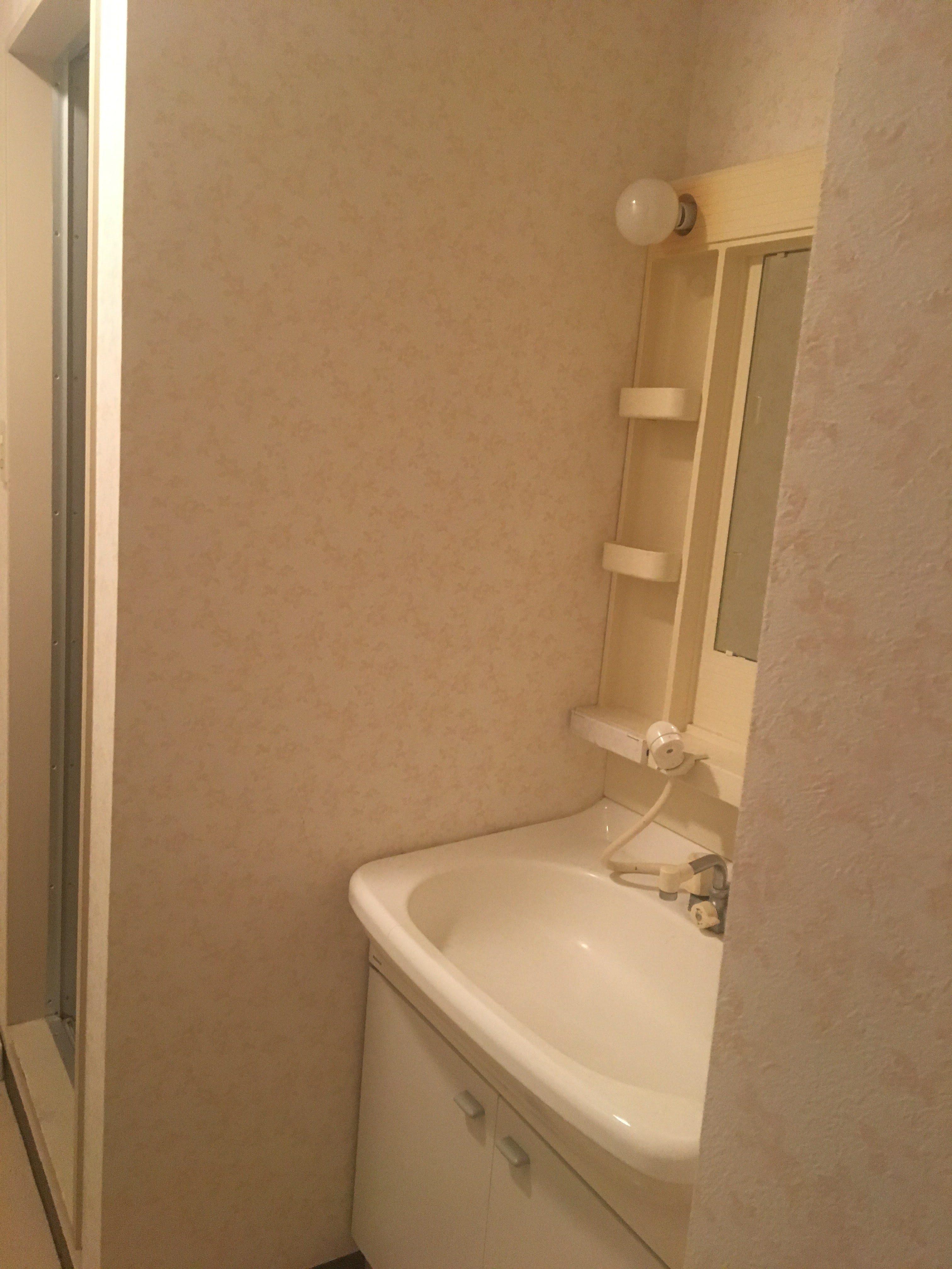 洗面台は一面鏡で、全体的に劣化しており、裸電球のままになっていた。
